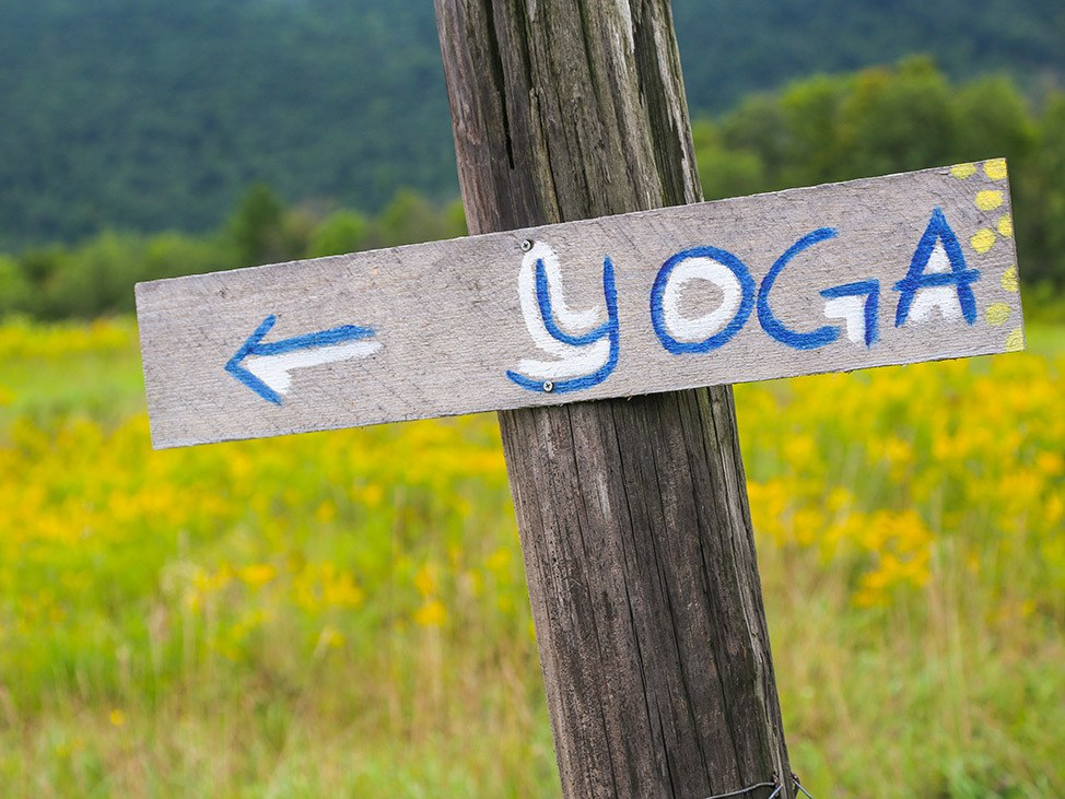 Wander Women Hudson Valley: hand painted sign for yoga class in pastoral field