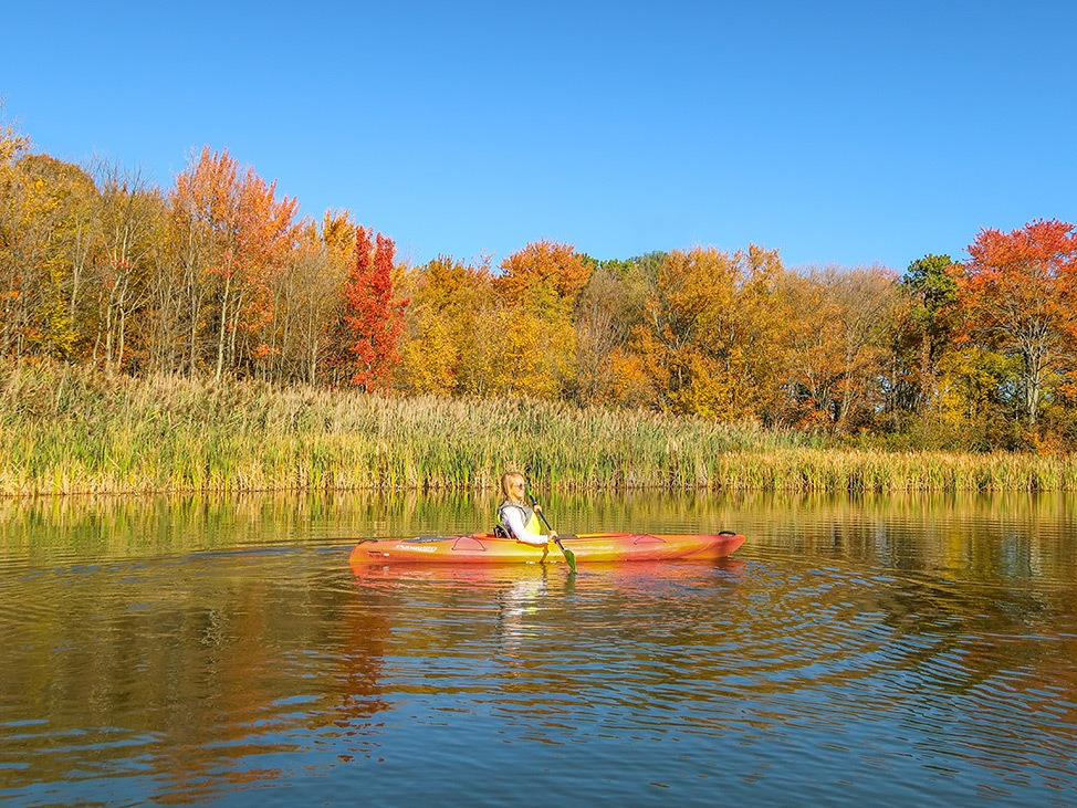 Wander Women Hudson Valley: Alex Baackes kayaking in fall foliage in upstate New York