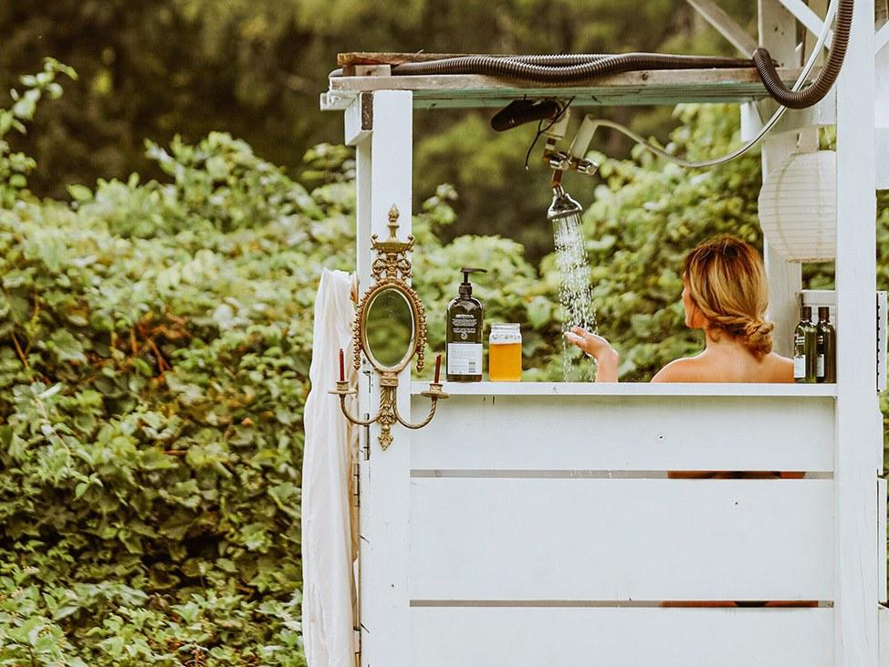 Wander Women Hudson Valley: woman taking outdoor shower in grassy area
